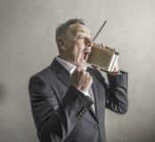 Zakenman die aan de radio luisteren die vreemde uitdrukkingen maken stock afbeelding