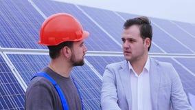 Zakenman die aan een arbeider op een achtergrond van zonnepanelen spreken stock videobeelden