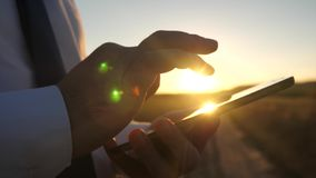 Zakenman die aan een tablet bij zonsondergang werken de handen van een mens drijven hun vingers over de tablet Close-up Mens royalty-vrije stock foto