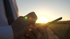 Zakenman die aan een tablet bij zonsondergang werken de handen van een mens drijven hun vingers over de tablet Close-up Mens stock foto