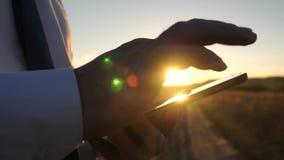 Zakenman die aan een tablet bij zonsondergang werken de handen van een mens drijven hun vingers over de tablet Close-up Mens royalty-vrije stock afbeeldingen