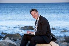Zakenman die aan laptop bij strand werken Stock Foto