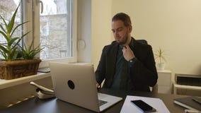 Zakenman die aan laptop in bureau werken die een band bevestigen stock video