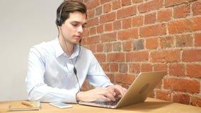 Zakenman die aan laptop computer in call centre werken stock footage