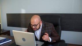 Zakenman die aan laptop computer in het bureau werken stock videobeelden