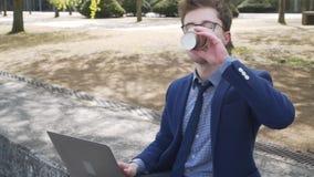Zakenman die aan laptop in de stad werken, steadicam schot stock videobeelden