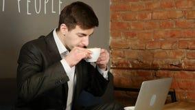 Zakenman die aan laptop en het drinken koffie op koffie werken stock videobeelden