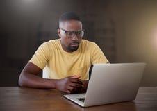 Zakenman die aan laptop met gele gloed in stad werken stock fotografie