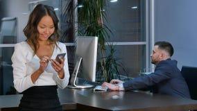 Zakenman die aan laptop, onderneemster werken die smartphone in bureau gebruiken stock afbeelding