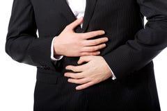 Zakenman die aan maagpijn lijden Stock Afbeeldingen