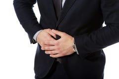 Zakenman die aan maagpijn lijden stock foto's