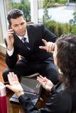 Zakenman die aan mobiele telefoon in vergadering luistert Stock Afbeeldingen