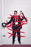 Zakenman die aan muur met bureaucratische formaliteiten wordt geplakt Stock Afbeelding
