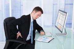 Zakenman die aan rugpijn bij computerbureau lijden Stock Foto