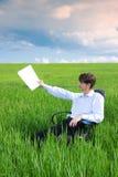 Zakenman die aan weide onder blauwe hemel werkt Royalty-vrije Stock Foto