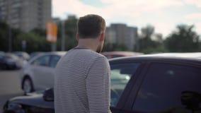 Zakenman die aan zijn auto op het parkeerterrein laat na het werk lopen stock videobeelden