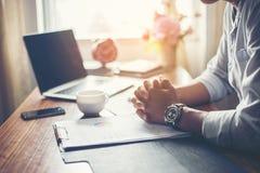 Zakenman die aan zijn bureau met een kop van koffie op kantoor werken stock afbeeldingen