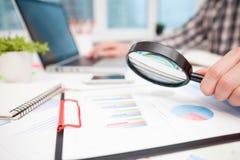 Zakenman die bedrijfsgrafieken met vergrootglas analyseren stock foto