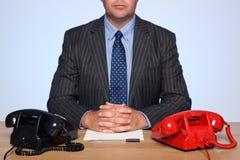 Zakenman die bij bureau met twee telefoons wordt gezeten. Stock Afbeelding