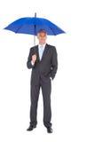 Zakenman die bij camera glimlachen en blauwe paraplu houden Royalty-vrije Stock Afbeelding