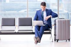 Zakenman die bij de luchthaven op zijn vliegtuig in bedrijfscla wachten stock afbeeldingen
