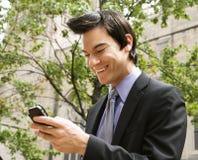 Zakenman die bij het bericht van de celtelefoon glimlacht. royalty-vrije stock fotografie