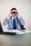 Zakenman die bij zijn bureau door verrekijkers kijkt stock fotografie