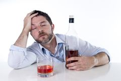 Zakenman die blauw die overhemd dragen bij bureau op witte achtergrond wordt gedronken stock afbeelding
