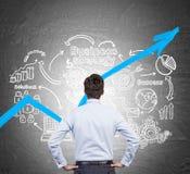 Zakenman die in blauw overhemd blauwe grafiek bekijken Stock Afbeeldingen