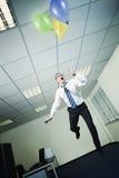 Zakenman die in bureau met ballons vliegt Royalty-vrije Stock Foto