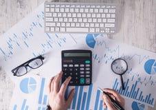 Zakenman die in bureau werken en calculator gebruiken stock afbeelding