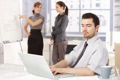 Zakenman die in bureauvrouwen werkt op achtergrond stock afbeelding