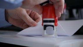 Zakenman die in Bureauzaal Officiële Bedrijfdocumenten en Contracten stempelen royalty-vrije stock foto's