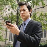 Zakenman die celtelefoon bekijkt. Stock Foto