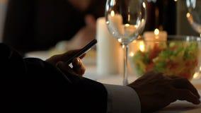 Zakenman die celtelefoon met behulp van om voor restaurantrekening, online bankieren app te betalen stock video