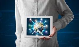 Zakenman die 3d aardebol in tablet voorstellen Stock Fotografie