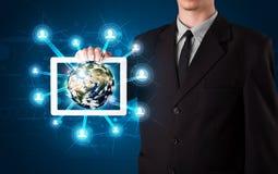 Zakenman die 3d aardebol in tablet voorstellen Royalty-vrije Stock Afbeelding