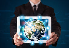 Zakenman die 3d aardebol in tablet voorstellen Royalty-vrije Stock Afbeeldingen