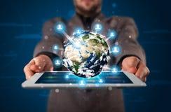 Zakenman die 3d aardebol in tablet voorstellen Royalty-vrije Stock Foto's