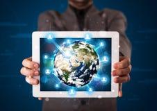 Zakenman die 3d aardebol in tablet voorstellen Stock Afbeeldingen