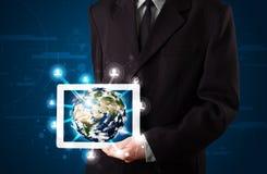 Zakenman die 3d aardebol in tablet voorstellen Stock Afbeelding