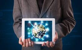 Zakenman die 3d aardebol in tablet voorstelt Stock Foto
