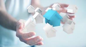 Zakenman die 3D teruggegeven kleine witte en blauwe huizen gebruiken Royalty-vrije Stock Afbeelding