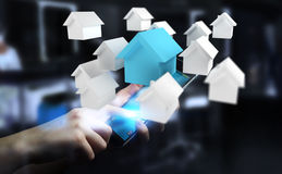 Zakenman die 3D teruggegeven kleine witte en blauwe huizen gebruiken Stock Afbeeldingen