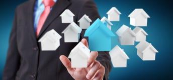 Zakenman die 3D teruggegeven kleine witte en blauwe huizen gebruiken Stock Fotografie