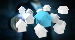 Zakenman die 3D teruggegeven kleine witte en blauwe huizen gebruiken Stock Foto's