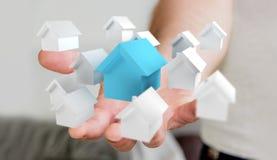 Zakenman die 3D teruggegeven kleine witte en blauwe huizen gebruiken Stock Foto