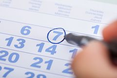 Zakenman die datum op kalender in bureau merken stock foto