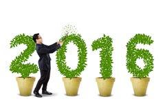 Zakenman die de boom gestalte gegeven aantallen 2016 snijden Royalty-vrije Stock Afbeelding