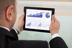 Zakenman die de effectenbeurs controleren op digitale tablet stock afbeelding